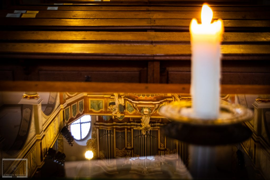 Reflections of historic church, candle and pews